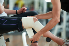Man Wrapping Bandage Around Knee. Young Woman With Injured Leg At Gym, Cropped Image. Sport, Fitness, People And Healthcare Concept.