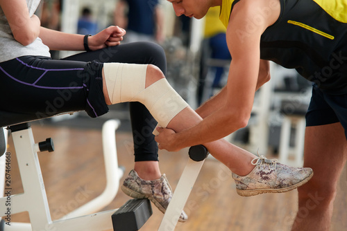 Man wrapping girls leg with bandage at gym Fototapete