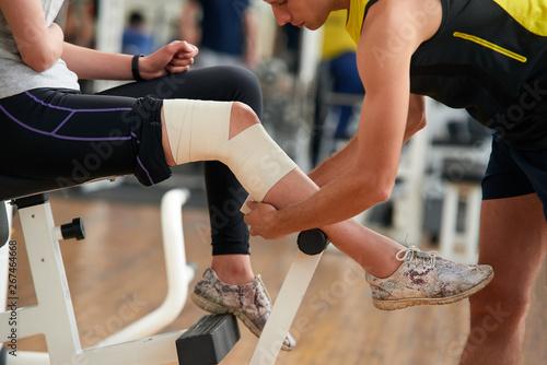 Foto Man wrapping girls leg with bandage at gym