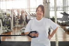 Happy Senior Woman In Gym Doin...