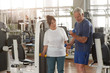 Elderly couple working out at gym. Senior man lifting dumbbells at fitness center. Sport activity for seniors.
