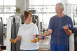 Caucasian senior people exercising at gym. Elderly couple lifting dumbbells together at fitness center. People, sport, healthy lifestyle.