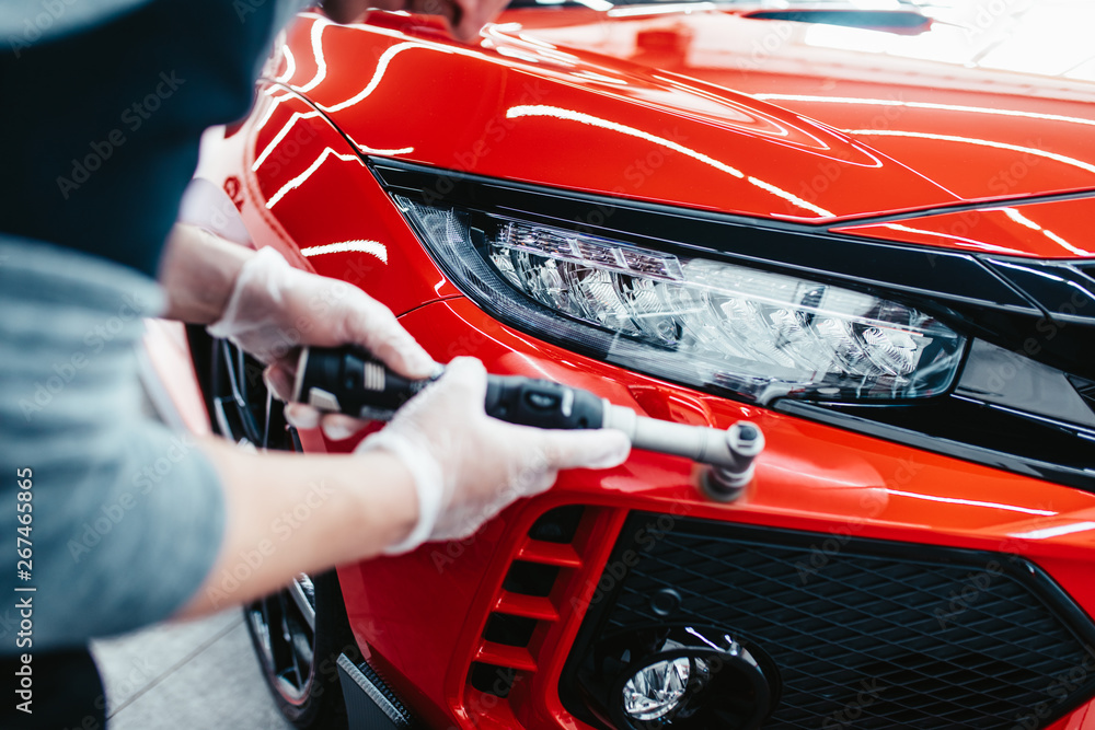 Fototapety, obrazy: Car detailing - Worker with orbital polisher in auto repair shop.