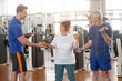 Personal trainer helping lift dumbbells to senior woman. Happy elderly couple lifting dumbbells while male instructor guiding them. Easy strength training workouts.