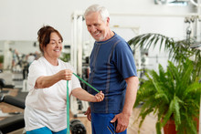 Beautiful Elderly Couple At Sport Club. Happy Senior Lady With Measuring Tape Showing Her Fitness Results At Fitness Club. People, Sport, Diet And Weight Loss Concept.