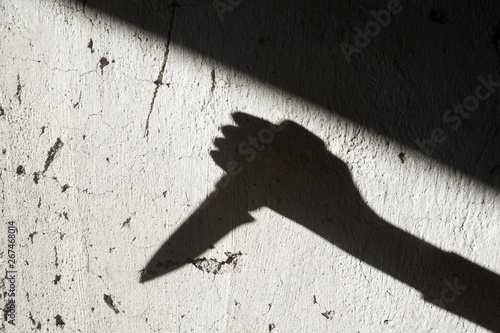 Fototapeta Shadow of the hand holding a knife