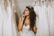 canvas print picture - Beautiful young woman choosing a wedding dress in a modern wedding salon.