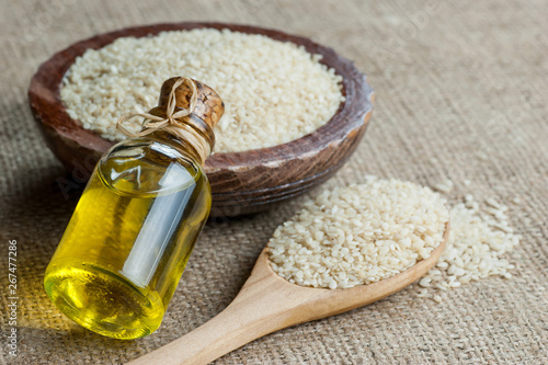Fototapeta Glass bottle of sesame oil and raw sesame seeds in wooden shovel and bowl on burlap sack. Uncooked sesame background concept with copy space obraz