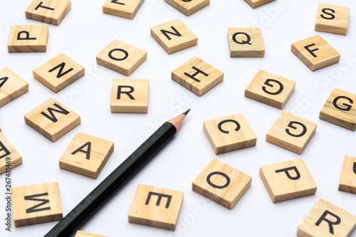 Black pencil and scattered alphabet letters on wooden blocks on white background Wallpaper Mural