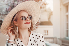 Outdoor Close Up Fashion Portrait Of Young Beautiful Happy Smiling Lady Wearing  Trendy Shell Earrings, Stylish Straw Wide Brim Hat, Sunglasses, Polka Dot Blouse, Posing In Street. Copy, Empty Space