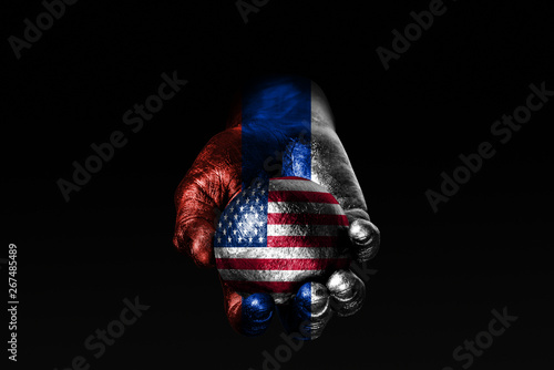 Canvas Print A hand with a drawn Russia flag holds a ball with a drawn USA flag, a sign of influence, pressure or conservation and protection