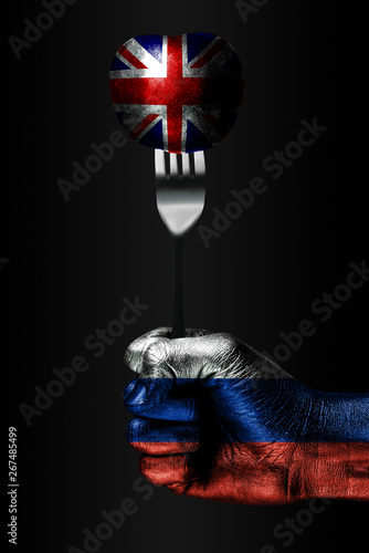 Canvas Print A hand with a drawn Russia flag holds a fork, on which is a ball with a drawn Great Britain flag, a sign of influence, pressure, grip and anecxia