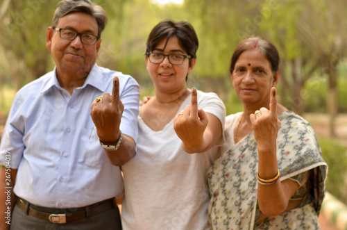 Poster Monkey Happy Family portrait - Senior Retired parents and their daughter showing the inked finger after voting in Indian elections in an outdoor park. Celebrating world's largest democratic elections concept