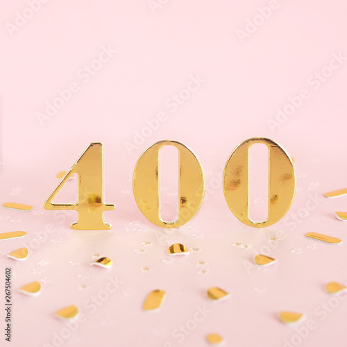 Tela  The number 400 is gold numbers on a pink background and golden confetti