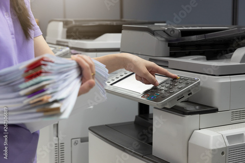 Canvas Print Bussinesswoman using copier machine to copy heap of paperwork in office