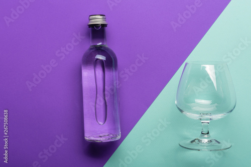 Foto op Canvas Alcohol transparent wineglass and bottle with water on bright purple and azure background