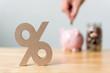 Leinwandbild Motiv Percentage sign symbol with blurred hand putting money coin in piggy bank