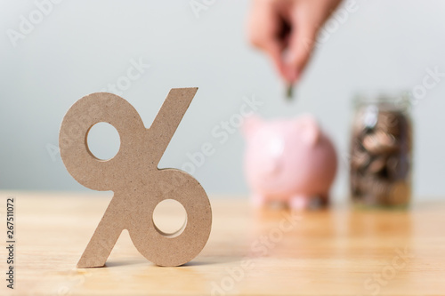 Fototapeta Percentage sign symbol with blurred hand putting money coin in piggy bank obraz