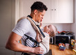 Leinwanddruck Bild - A father with small toddler son in carrier in kitchen indoors at home.