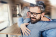 canvas print picture - An adult hipster son and senior father indoors at home, hugging.