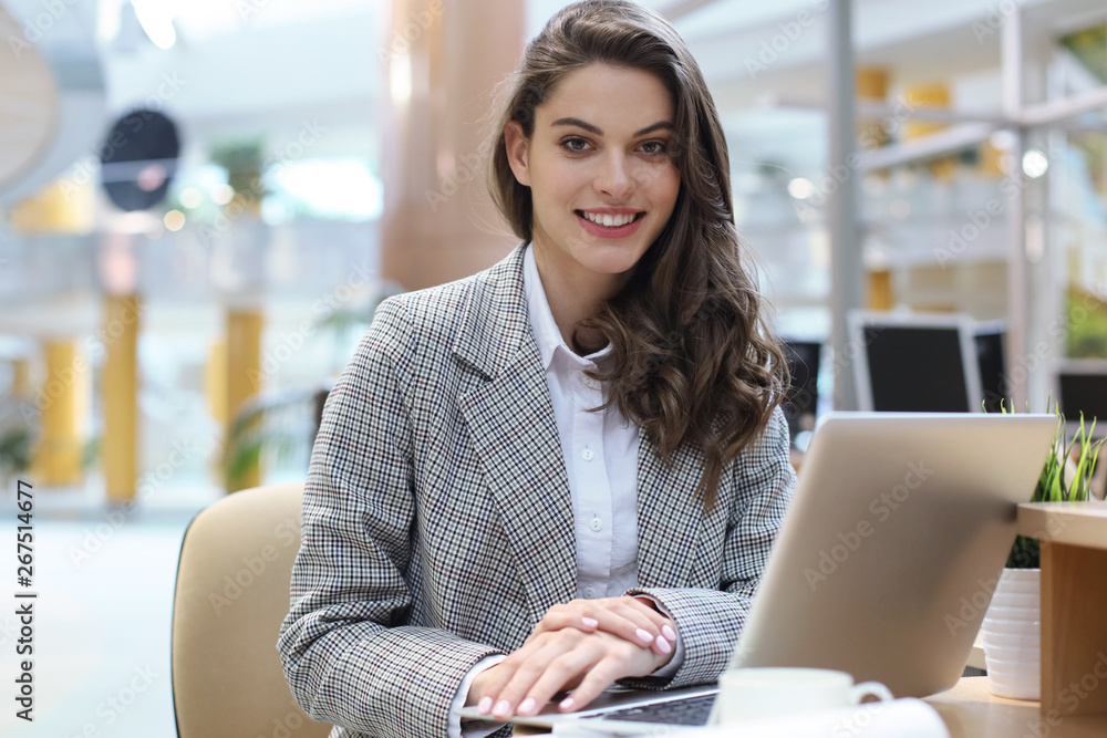 Fototapeta Portrait of a cheerful young businesswoman sitting at the table in office and looking at camera.