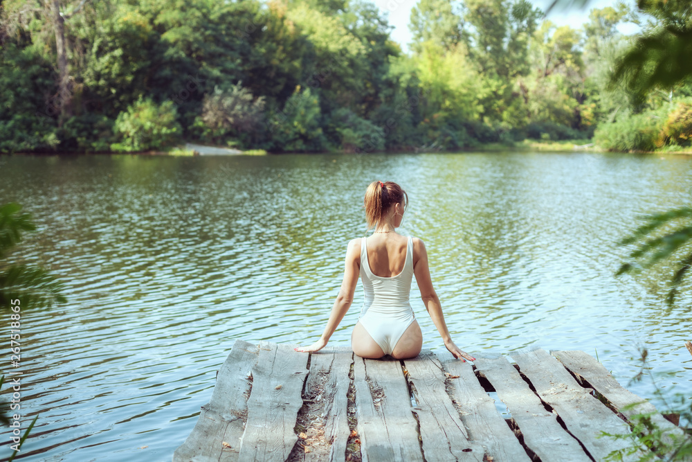 Fototapety, obrazy: Beautiful woman in nature on the lake, she relaxes.