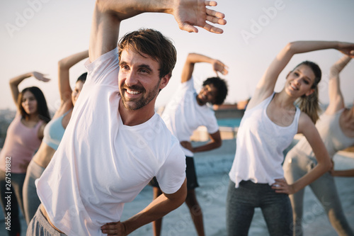 Fototapeta Fitness, sport, friendship and healthy lifestyle concept . Group of happy people exercising obraz