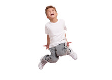 Adorable Little Boy Smiling And Jumping, Isolated On White Background. Shooting In The Studio.
