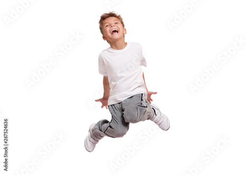 Fotografie, Tablou Adorable little boy smiling and jumping, isolated on white background
