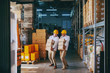 Two blue collar workers in white uniforms and with yellow helmets on heads relocating heavy boxes in warehouse.