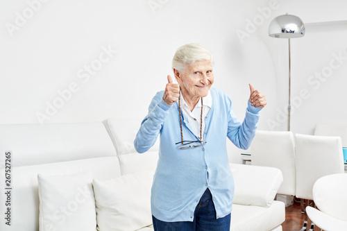 Fotografia  Optimistische alte Frau hält die Daumen hoch