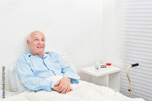 fototapeta na szkło Senior liegt bettlägerig im Bett im Krankenhaus