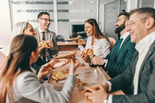 Small Group Of Happy Colleagues In Formal Wear Chatting And Eating Pizza Together For Lunch. Alone We Can Do So Little, Together We Can Do So Much.