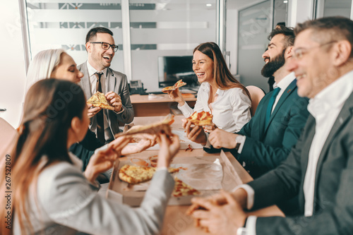Stampa su Tela Small group of happy colleagues in formal wear chatting and eating pizza together for lunch
