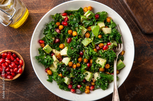 avocado, kale, roasted chickpeas, almond and pomegranate salad in white bowl Fototapete