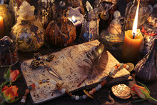 Witch Book With Cross, Quill, Burning Candles And Magic Bottles On The Table.