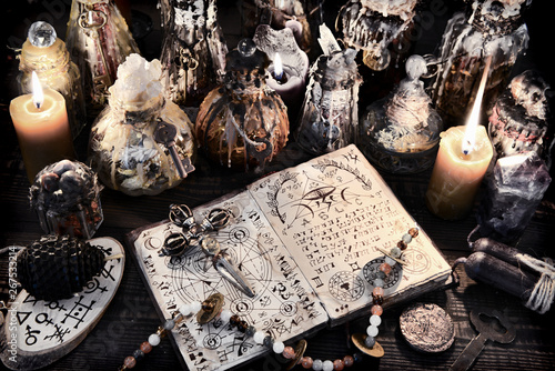 Leinwand Poster  Open magic book with ancient symbols, witch bottles and black candles