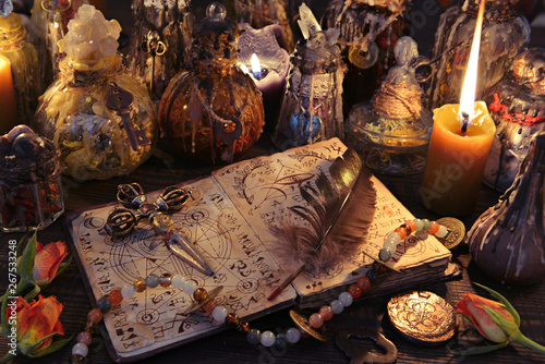 Witch book with cross, quill, burning candles and magic bottles on the table Fotobehang