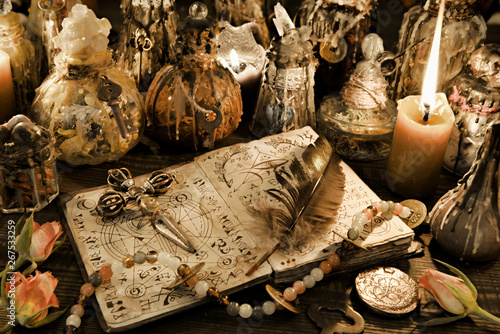 Fotografie, Obraz Magic ritual bottles with open witch book, quill and cross in candlelight on the