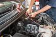 Auto mechanic repairing in a car