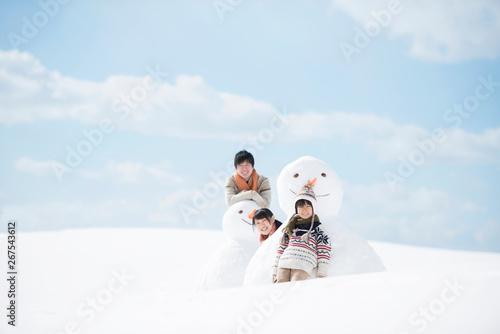 Fotografia  雪だるまの側で微笑む家族