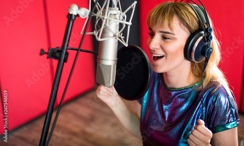 Fotografie, Obraz  Female with microphone recording a voice for dubbing in music studio