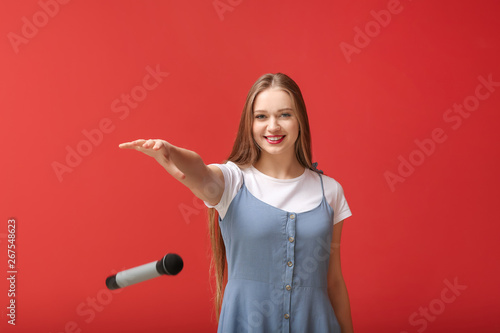 Beautiful woman dropping microphone on color background