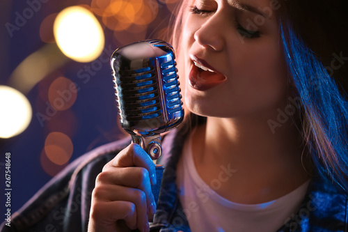 Beautiful female singer with microphone on stage, closeup - 267548648