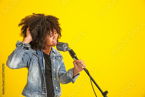 Valokuva  African-American girl with microphone singing against color background