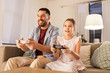 Leinwandbild Motiv family, gaming and entertainment concept - happy father and little daughter with gamepads playing video game at home