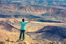 A Man With Hands In The Air Standing On The Cliff In The Desert