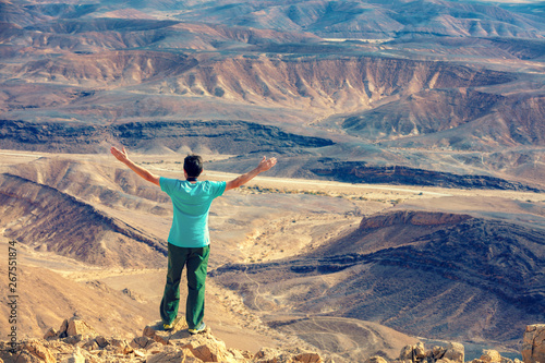 Foto auf Gartenposter Beige A man with hands in the air standing on the cliff in the desert