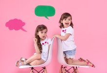 Two Little Girls On Colored Background With Speech Icons