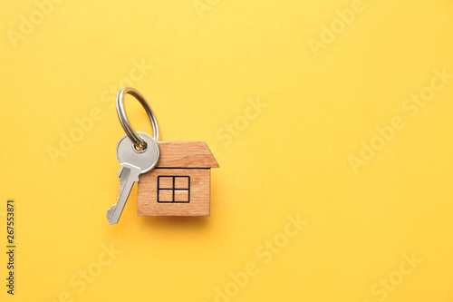Fotografía  Key with trinket in shape of house on color background